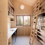 Svetlá drevená pracovňu s vysokou knižnicou
