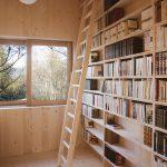 Svetlá drevená knižnica s rebríkom v chate