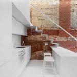 Tehlová stena v bielej kuchyni so schodiskom
