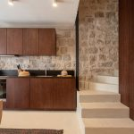 Tmavohnedá kuchyňa a schodisko na poschodie