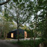 Chata s veľkými oknami ukrytá v lese