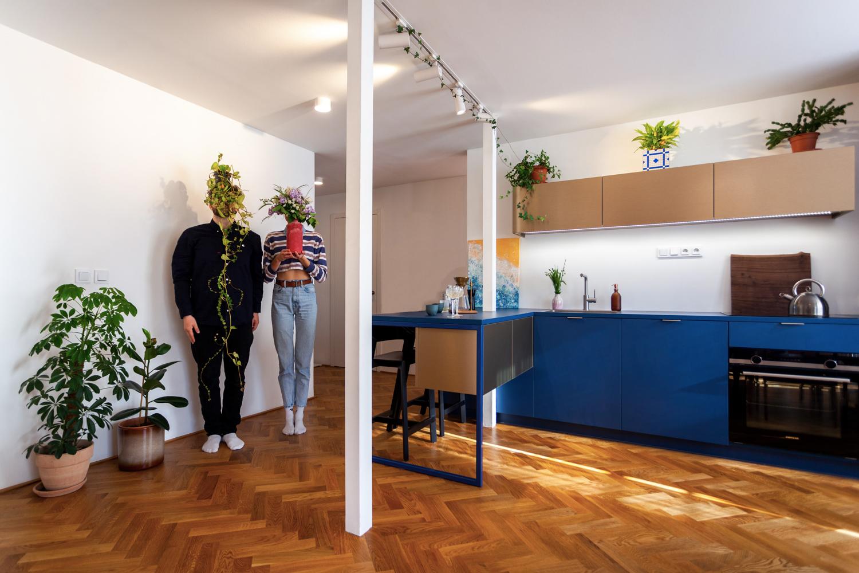 Modrá kuchyňa s parketami a pár s kvetináčmi pred hlavami