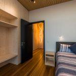 Spálňa s drevenou podlahou a skriňou