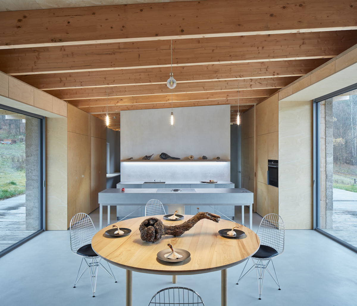Sivá kuchyňa a jedáleň v drevenom interiéri
