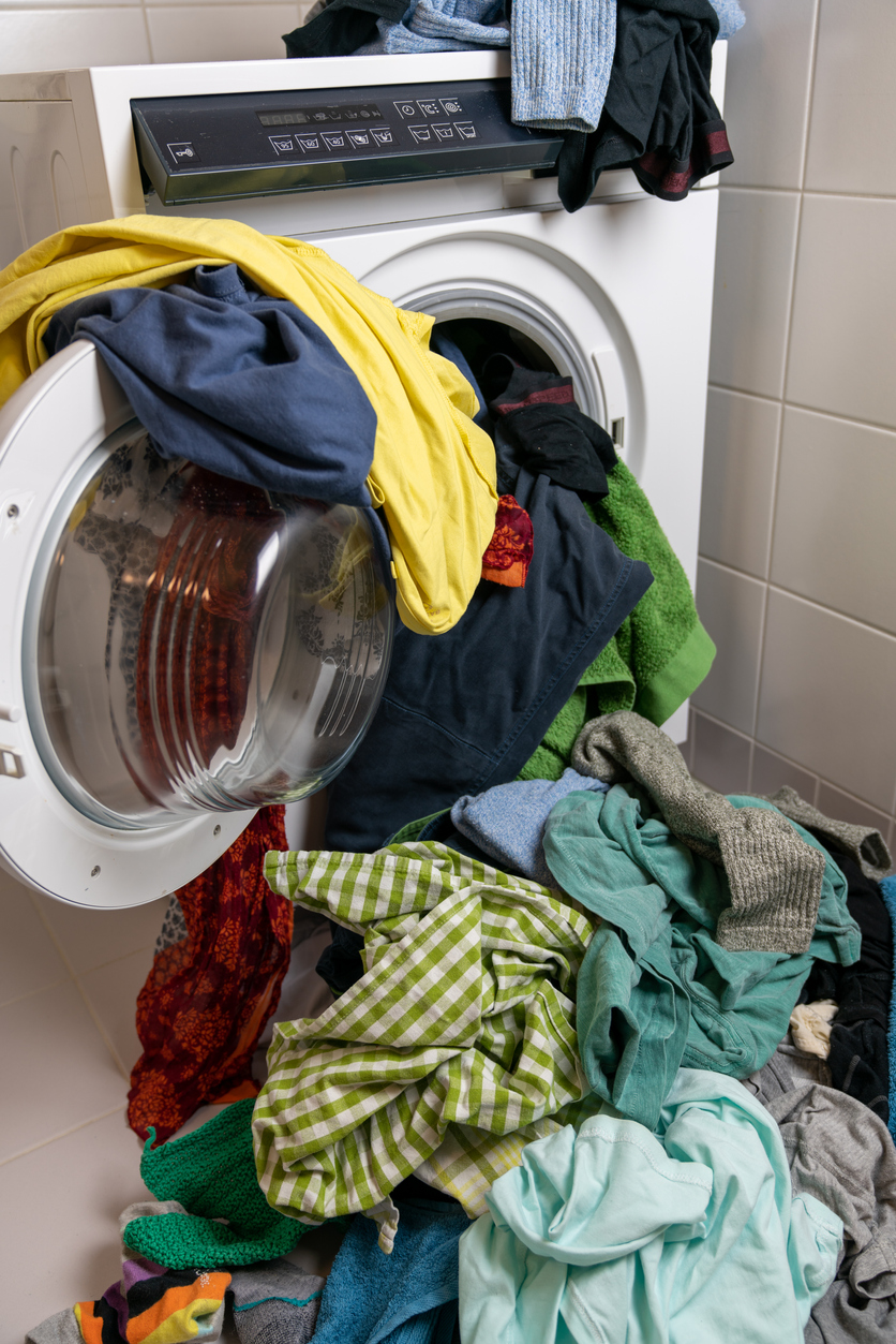 Giant pile of colorful dirty laundry and a washing machine stuffed full with clothes