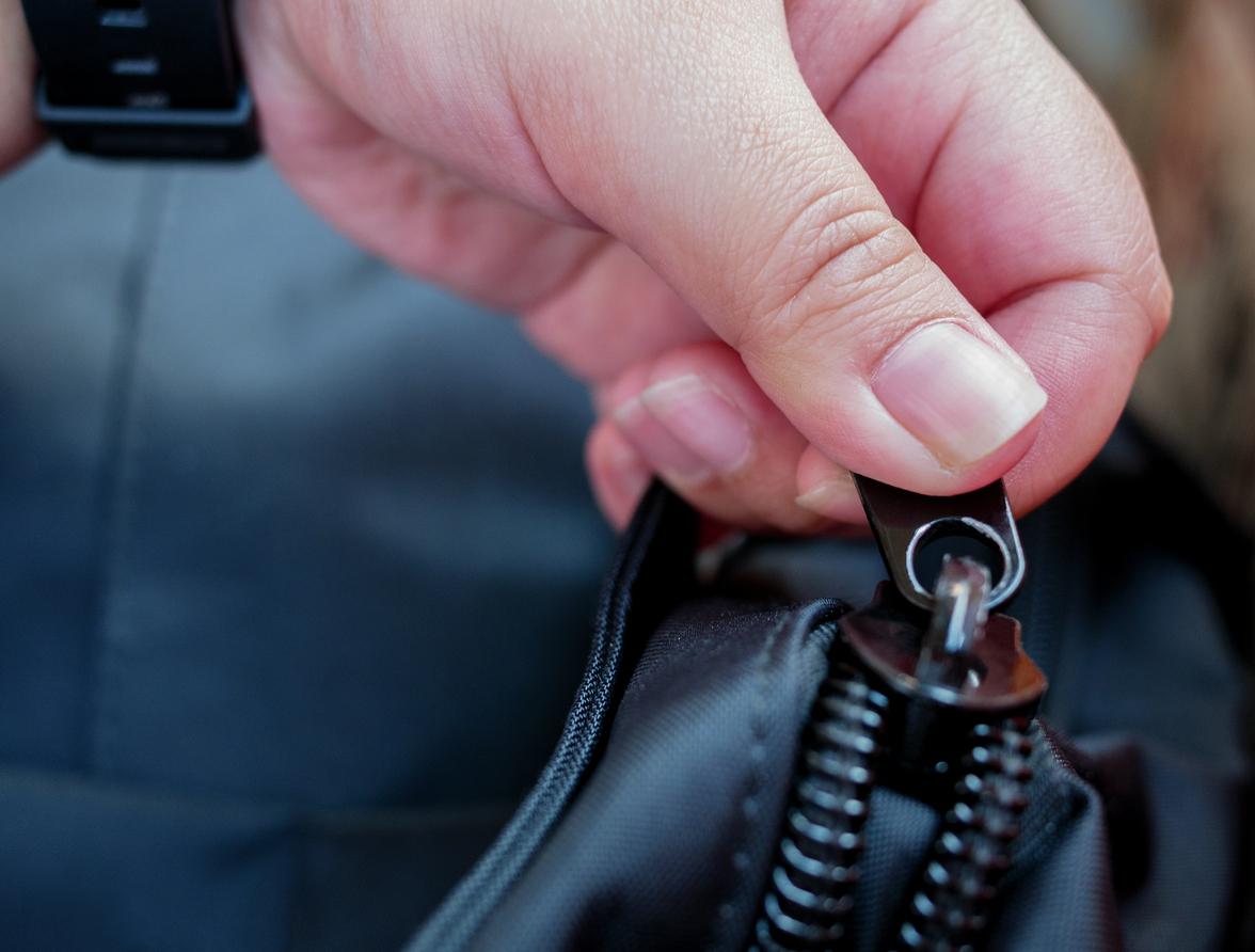 Hand holding bag zipper to open