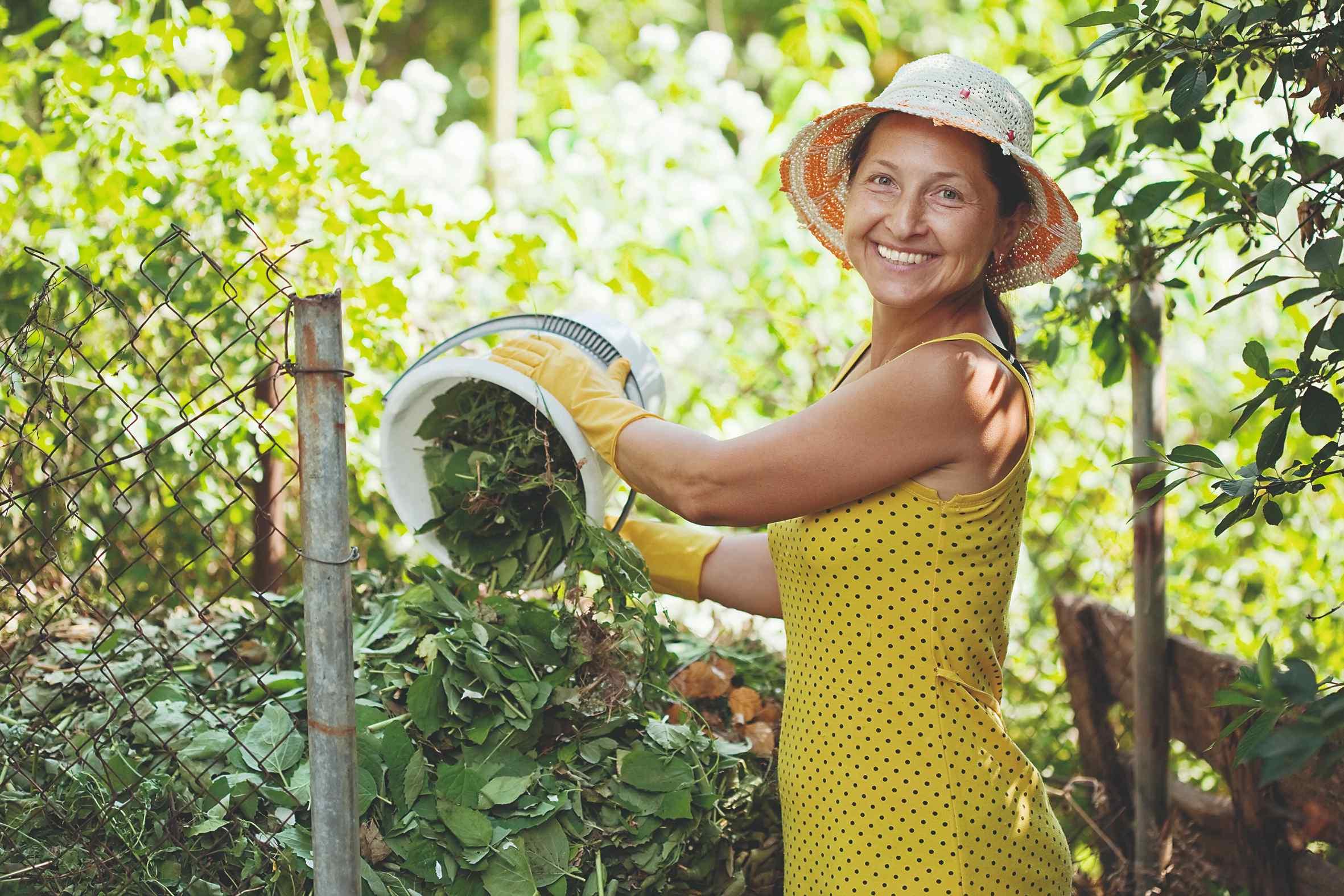 Žena vysýpa do kompostéra v záhrade