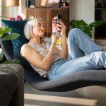 Žena leži v kresle a pozerá do telefónu