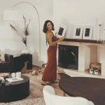 Žena pri krbe v obývačke držiaca rám s fotografiou