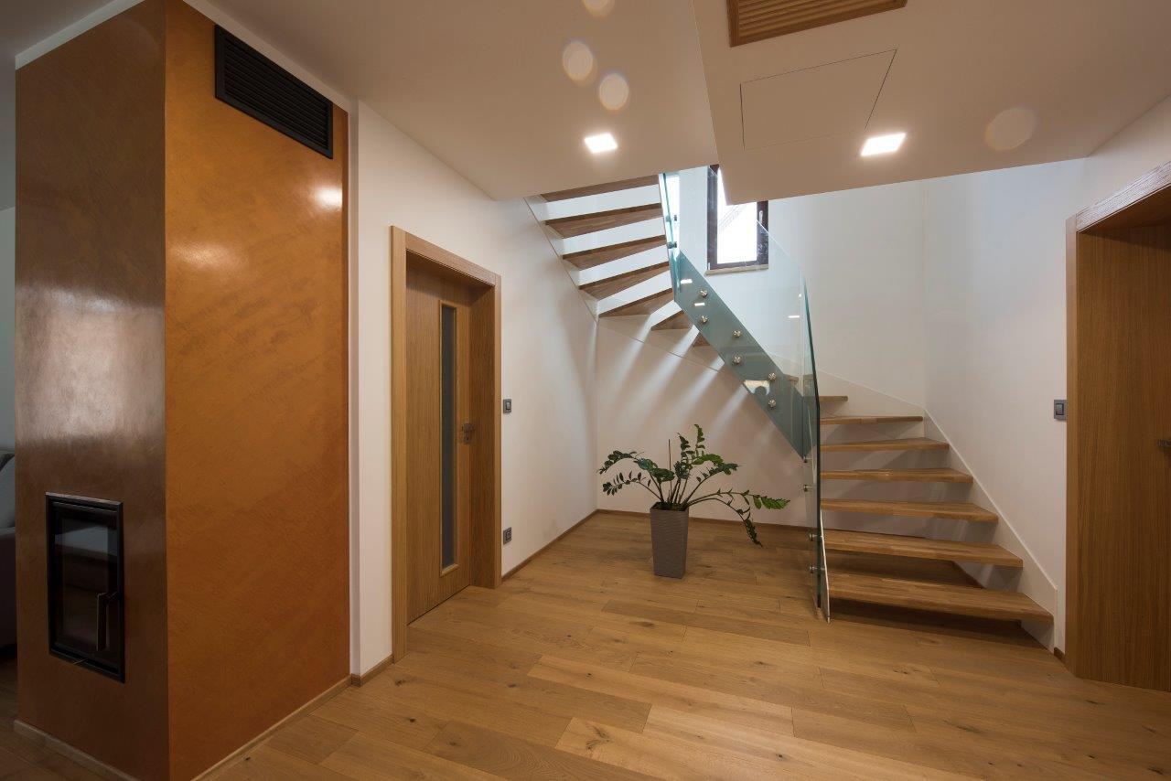 Interiér domu s drevenou podlahou, schodišťom a dverami