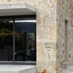 Kamenná stena s presklením a psom