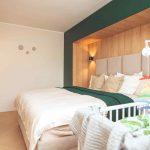 Posteľ typu boxspring v spálni s drevenou stenou