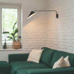 Tmavozelený gauč pri bielej tehlovej stene