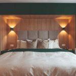 Posteľ typu boxspring v spálni so zelenou stenou
