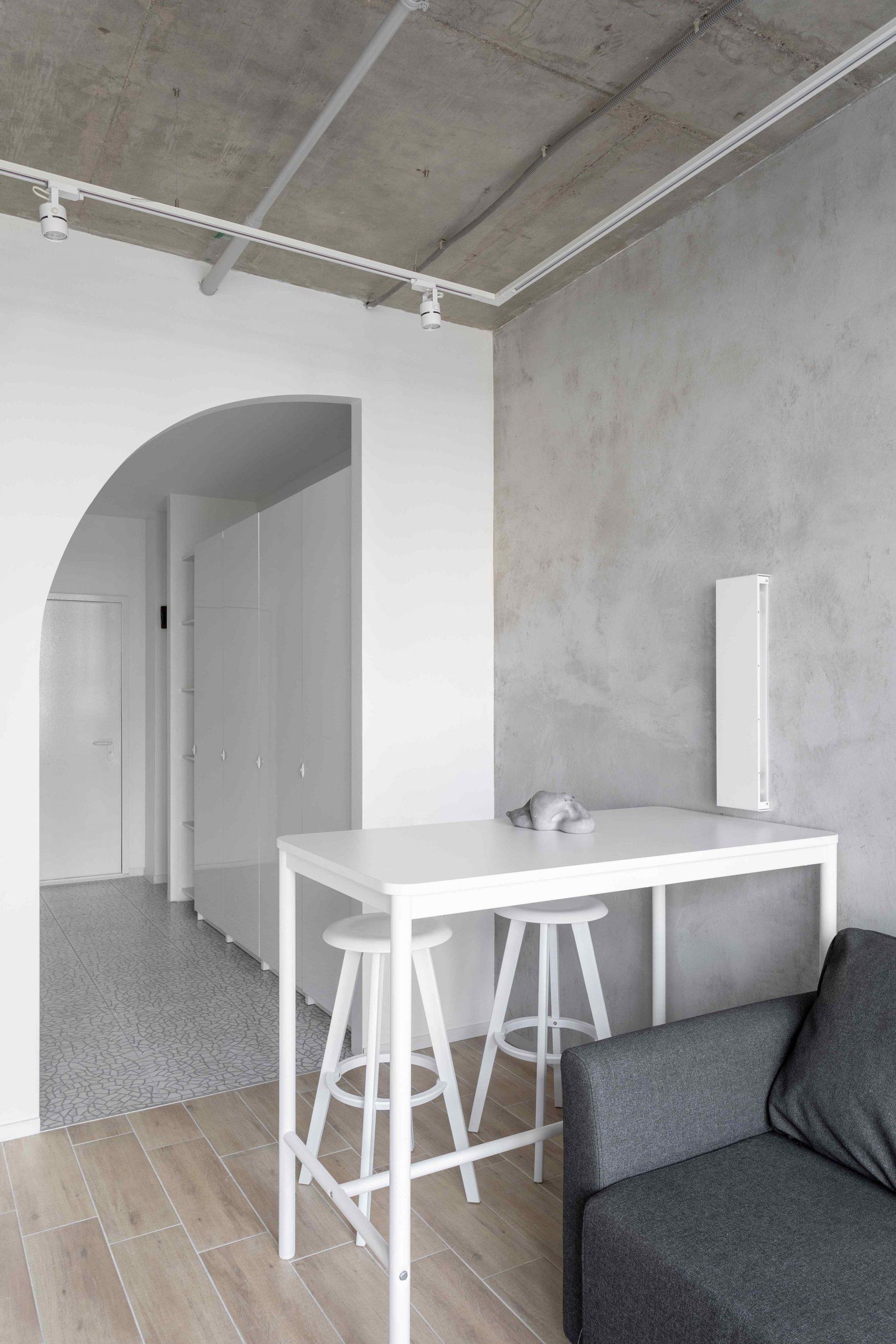Stolík s barovými stoličkami pred oblúkom do chodby