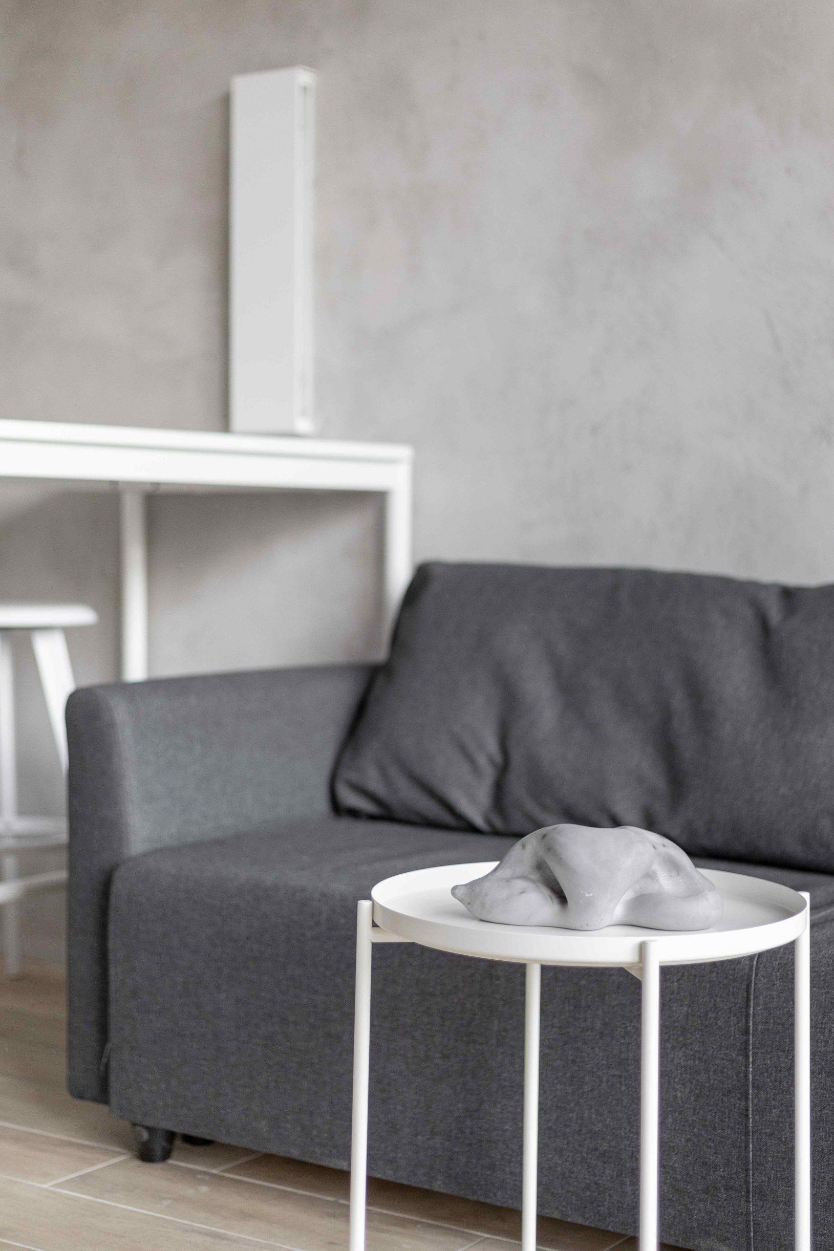Sivý gauč so stolíkom a sochou v popredí