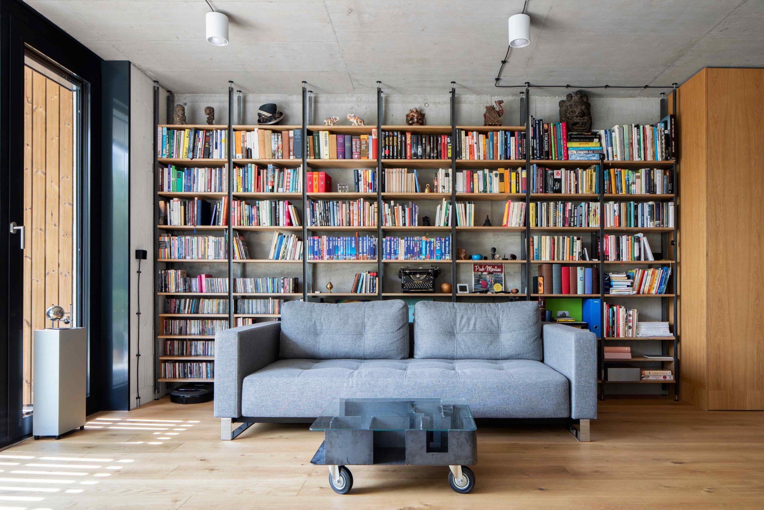 Obývačka s veľkou knižnicou sivým gaučom a betónovým stropom