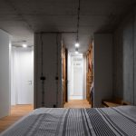 Spálňa s betónovým stropom a šatníkom