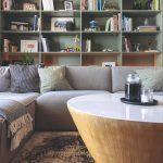 Zelená policová stena v obývačke so sivým gaučom