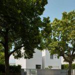 Hranatý biely dom za stromami