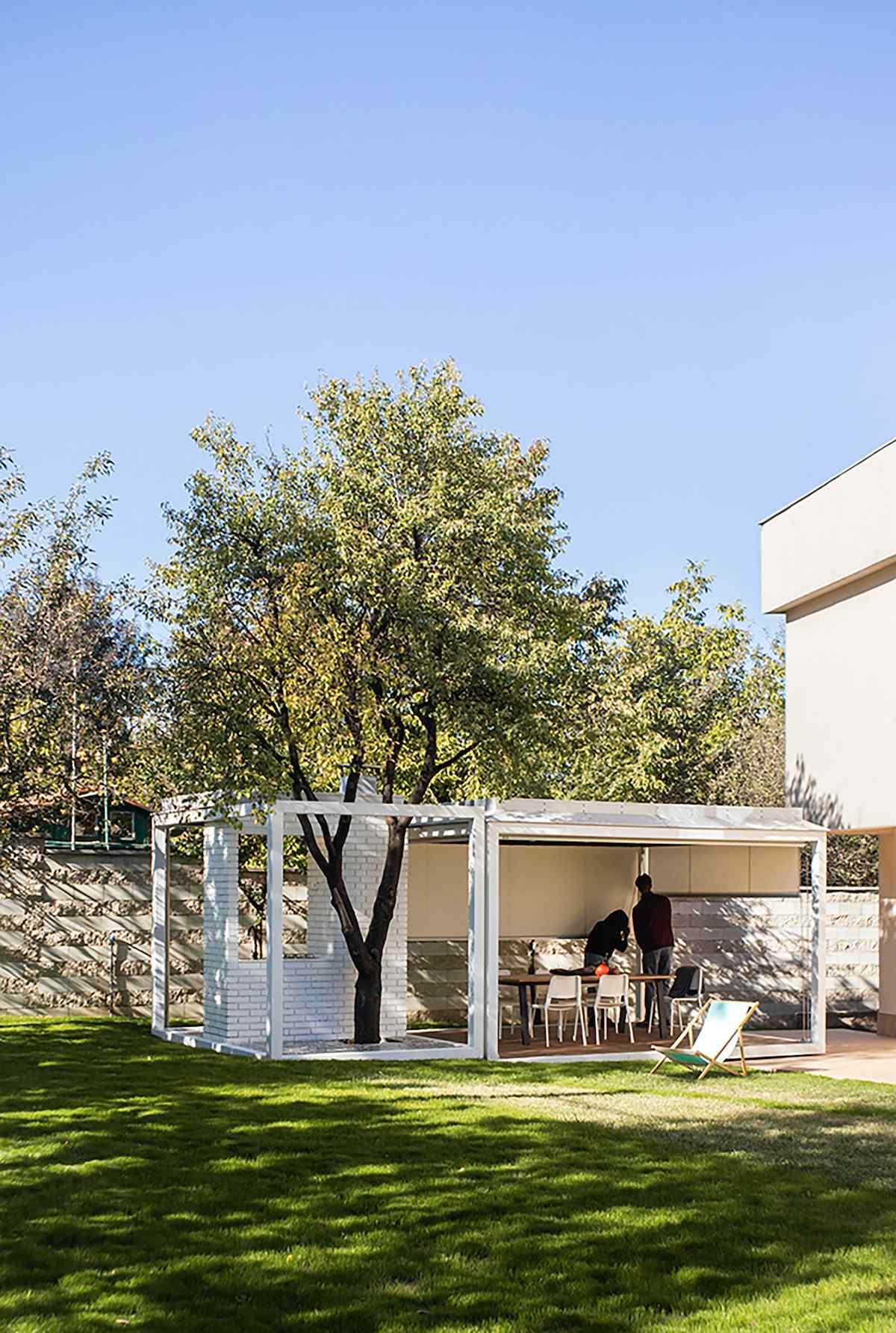 Pavilón v záhrade domu so zabudovaným stromom