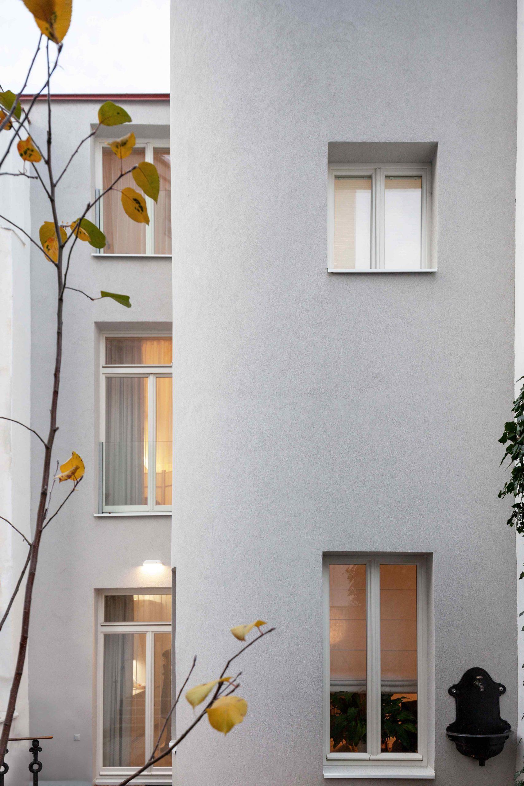 Biely trojpodlažný dom s francúzkymi oknami