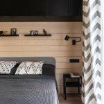 Tmavá spálňa v stodole s drevenou stenou