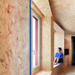 OSB dosky v obývačke vo veľkých oknách sediaca žena
