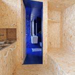 Pohľad z drevenej kuchyne do žiarivo modrej kúpeľne