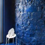 Modrá lesklá živica na stene biely stolček