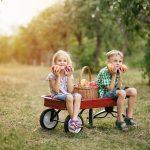 Deti sediace na vozíku v jablčnom sade
