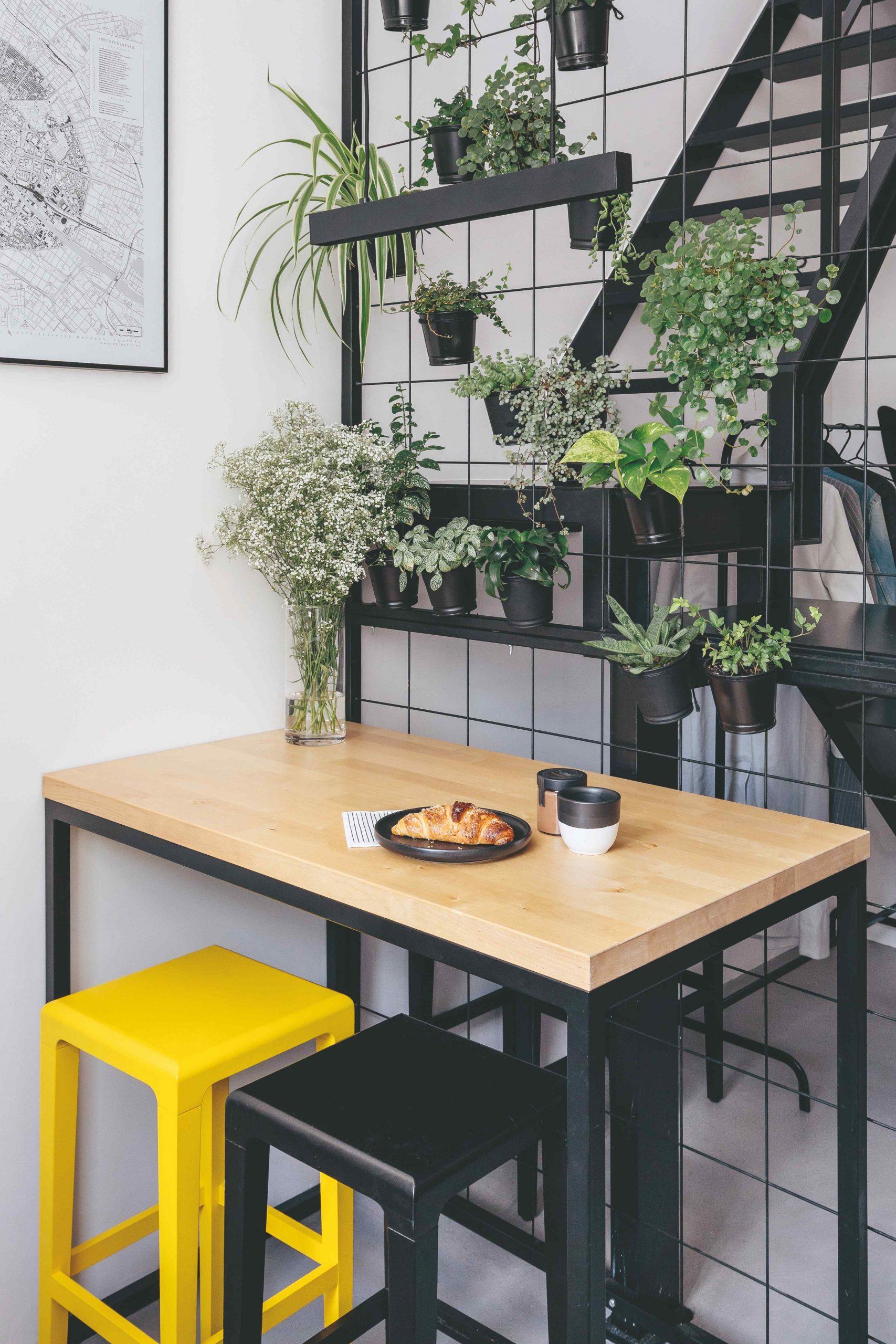 Barový stôl s farebnými stoličkami pri kvetinovej stene