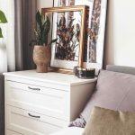 Biela komoda s opretými obrazmi v spálni