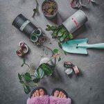 Plechovky kvetiny a náradie na zemi pri ženských nohách