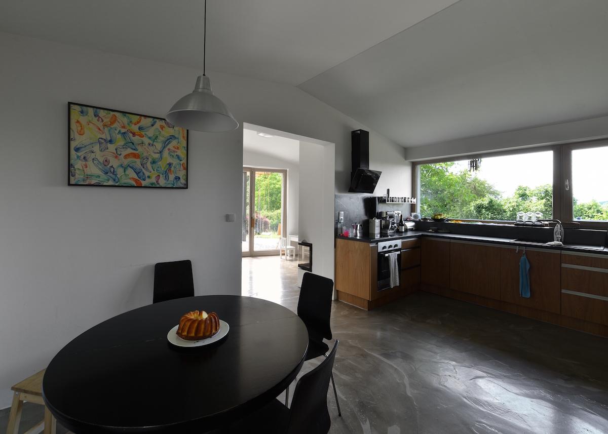 Kuchyňa s čiernym jedálenským stolom a veľkým oknom
