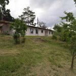 Sivý jednopodlažný rodinný dom na zarastenom kopci