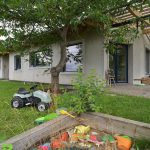 Sivý jednopodlažný rodinný dom s pieskoviskom