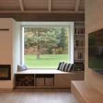 Obývačka s veľkými oknami so sedením a s výhľadom do lesa