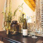 Stolík v chodbe so zrkadlom a fľašou vína