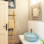 Kúpeľňa s modrým umývadlom a gotickým zrkadlom